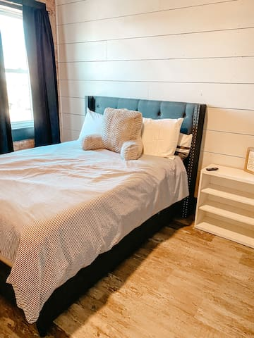 Bedroom two features full size mattress, blackout curtains and wall-mounted smart tv.