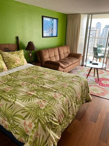 Comfortably Hawaii themed living space with queen sized bed and couch that folds out into double bed.