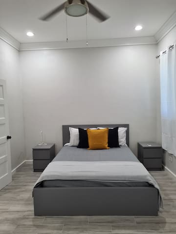 This bedroom has a queen-sized bed and shares a common bathroom that can be accessed from inside the room. It has a window facing the front yard, so you'll have morning light to wake you gently. It has a large closet, resting chair and mirror. AC too