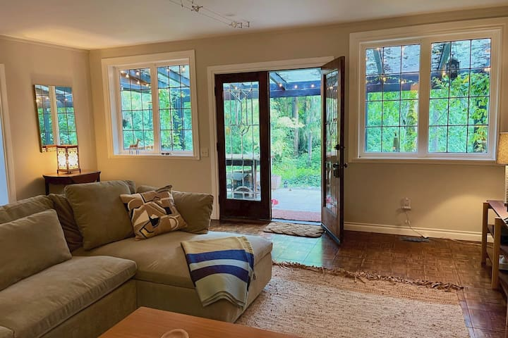 Living room opening onto an adorable covered front porch with expansive views of lush, private forest ravine. Sip coffee and watch the hummingbirds at dusk!