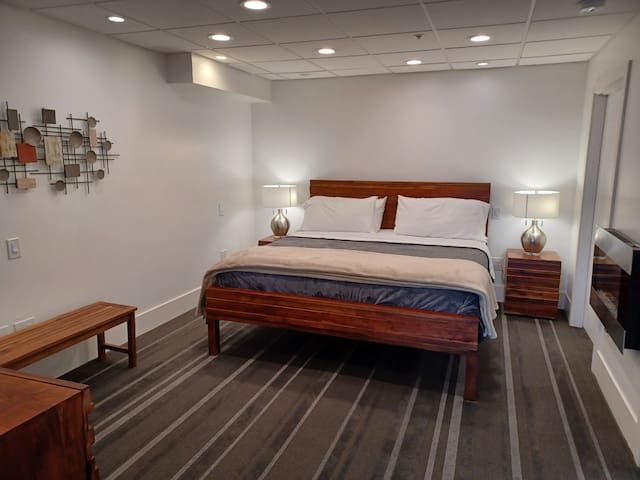 In the bedroom- King size bed, beside electric fireplace, West Elm bedroom set, and mulitple lighting options with dimmers
