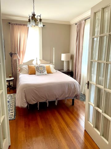 The roomy bedroom features plenty of natural light, a new, queen-sized bed, antique vanity, and an en suite full bath.