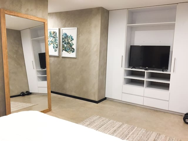 Smart TV with Roku, easy to connect to your favorite apps or AirPlay movies from your devices. Enjoy a beautiful full length mirror with natural light coming in from the bedroom's private balcony. This is also my favorite space to work out!