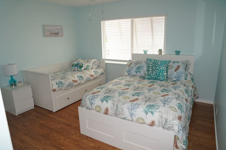Bedroom with queen bed and single bed with tv and large closet