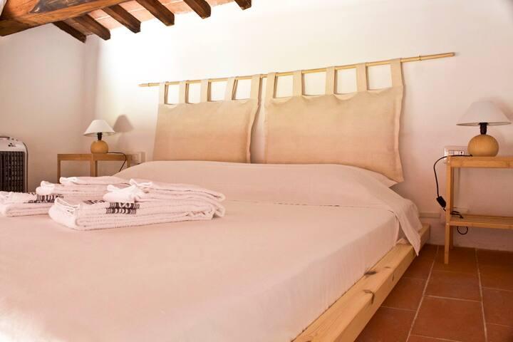 Il letto sul soppalco con le travi è un nido romantico e particolare