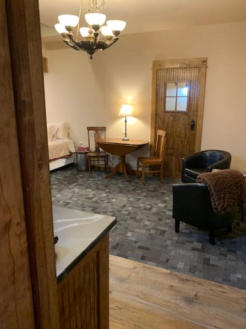 From the bathroom doorway, the dining table, chairs and king bed are seen. The counter to the left is the kitchenette.
