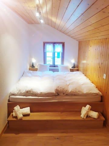 Chambre avec un lit double 180x200 cm et un petit salon