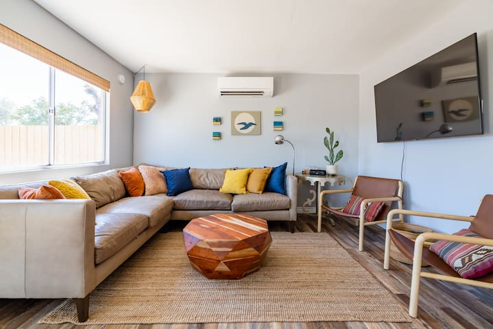 """The open living area invites you to spend time together while lounging, listening to music, or watching a movie on the new 65"""" Samsung Smart TV"""