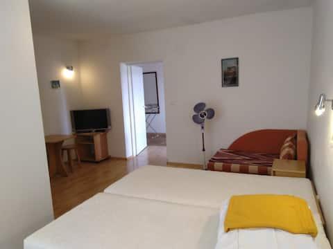 Izba s vlastnou kúpeľňou a zdielanou kuchyňou, s terasou,  balkónom a posedením pod stromom.