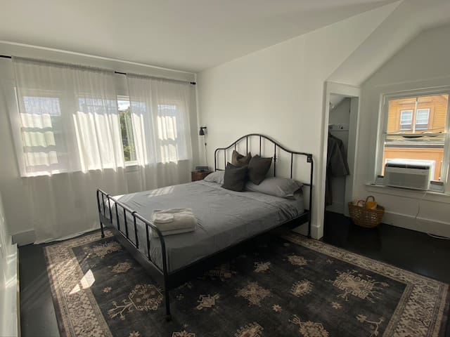 Bedroom 1 (king size bed), bay windows overlooking Commercial street. AC window unit. Designated work space with desk. Dresser and closet to make yourself at home.