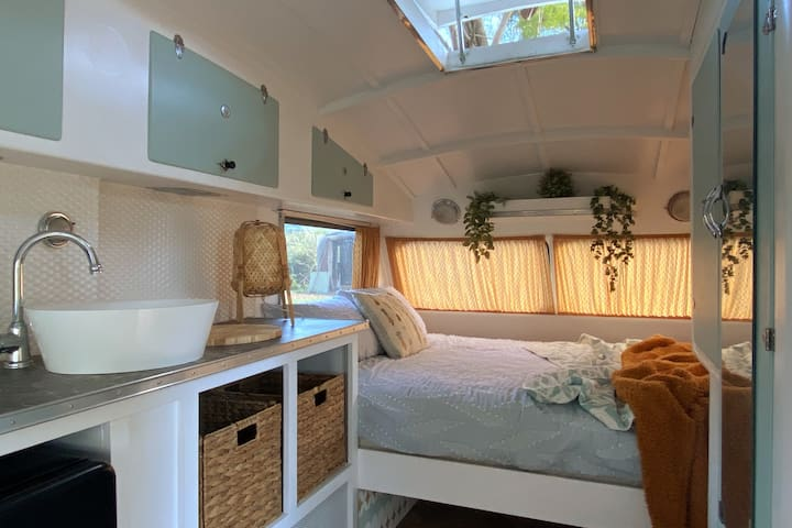 The extra queen bed, located in the nearby vintage Roadmaster caravan