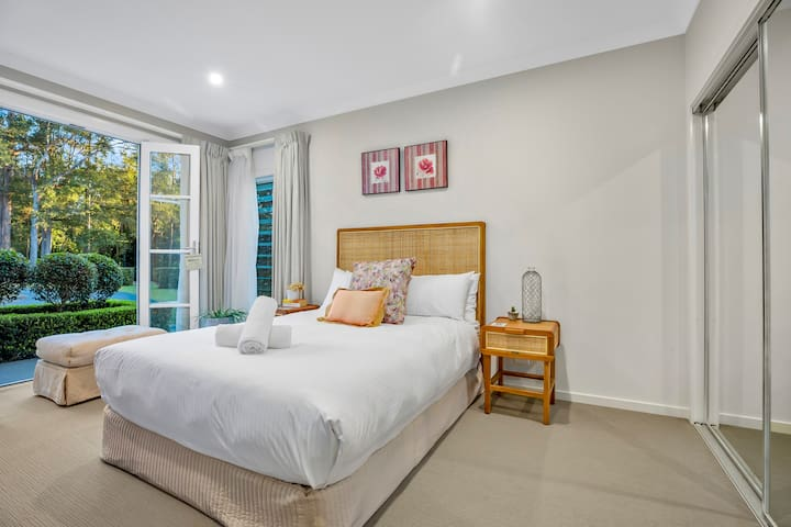 The stunning fourth bedroom is located downstairs with classic French doors opening to the garden. It has a queen-sized bed.