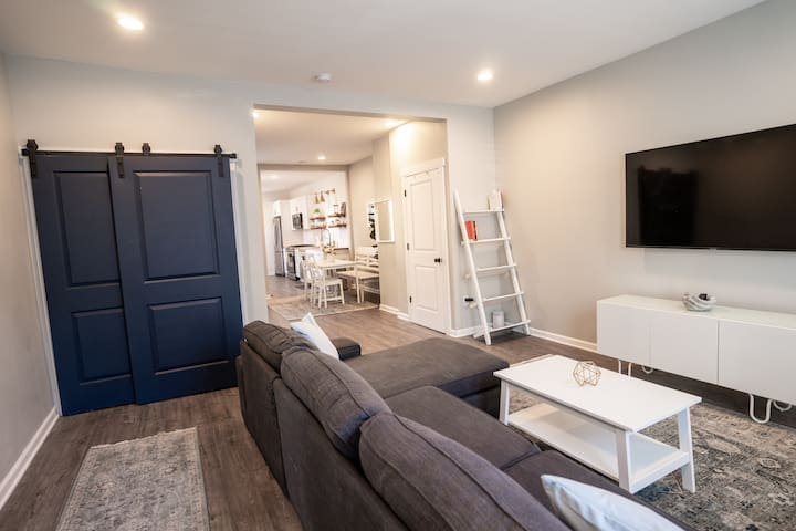 Living room with smart TV, our favorite books, Samsung washer/dryer, behind the blue barn doors.