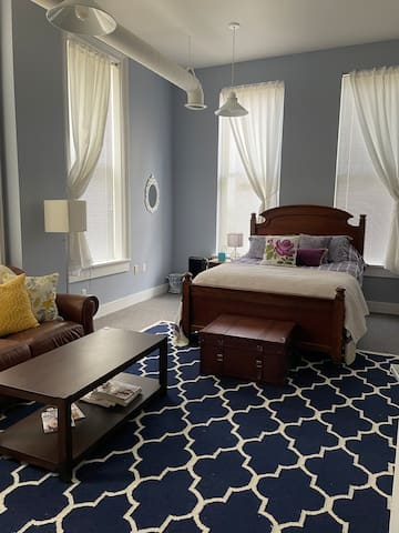 Extra large bedroom with one queen and 2 twins. Picture is of queen bed and seating area. Room has smart TV in armoire.