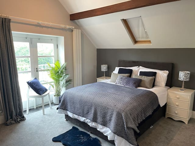 Master bedroom. King size bed. Built in wardrobe and chest of drawers. French doors onto Juliette balcony overlooking sports fields.