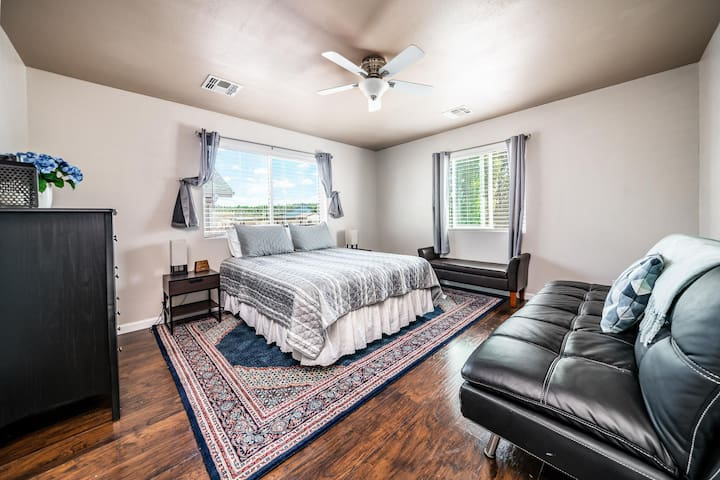 The roomy master bedroom with queen bed, features a leather futon and storage bench. All bedside lamps and clocks include USB charging ports.