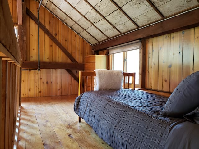 Each of the smaller loft bedrooms include a twin bed, dresser, and bedside table.