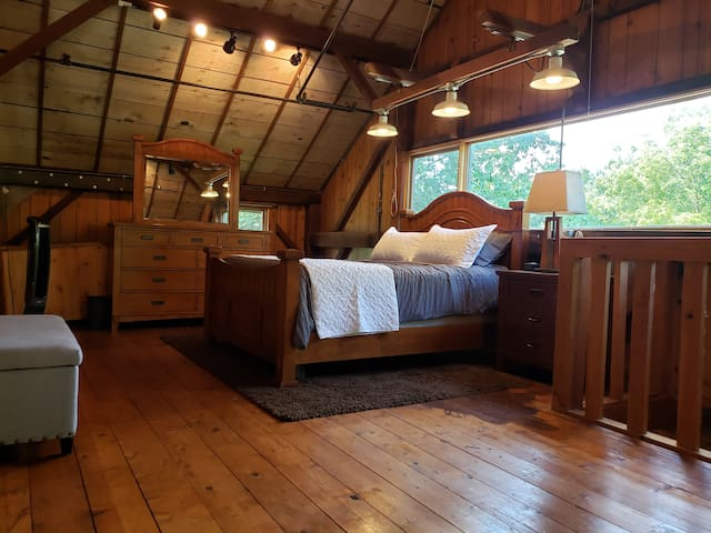 The main bedroom loft includes a queen pillow top bed, nightstand, dresser, alarm clock and rotating fan.