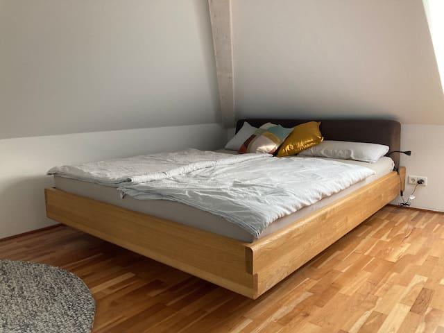 Schlafzimmer mit metallfreiem Bett von team7 in den Maßen 180 x 220 cm