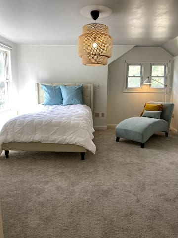 Second-floor suite with queen sized bed, chaise, closet, and bathroom.