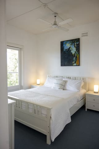 The bright second bedroom is furnished with a queen bed topped in quality linen and features a ceiling fan, bedside tables and a timber tallboy