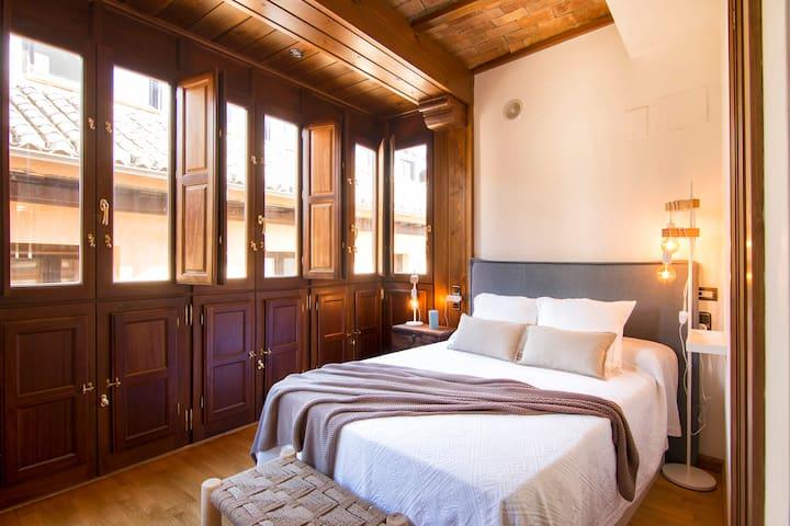 El dormitorio conserva los techos de revoltones originales del edificio, y tiene una iluminación espectacular gracias al lateral acristalado emarcado en carpintería de iroko.