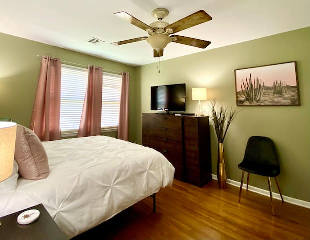 Queen bed with dresser and TV