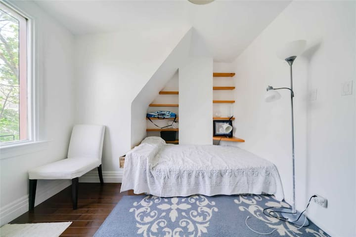 Beautiful, bright bedroom with large window facing quiet street, built in shelves, clothing rack