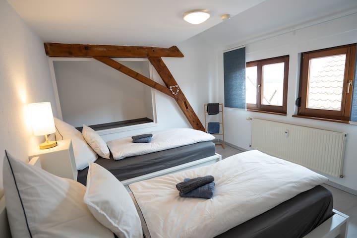 Gäste-Schlafzimmer mit zwei 90x200cm Betten und hohen Taschenfederkernmatratzen. Mit offenem Kleiderschrank für die Ablage von Koffer, Wäsche, etc.