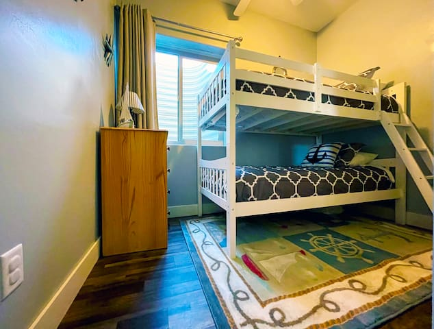 The third bedroom on the lower floor features bunk beds for the kids.