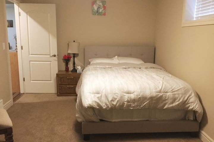 Our second spacious bedroom includes a queen bed, nightstand, dresser, laundry hamper, chair and a standing mirror.