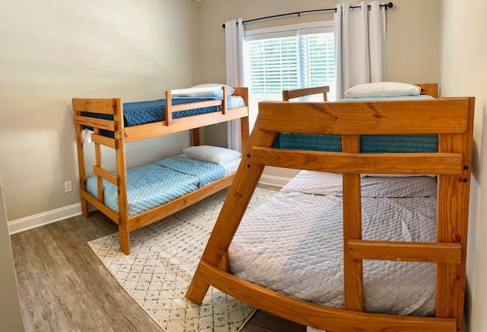 Bunk room with 1 full bed and 3 single beds.