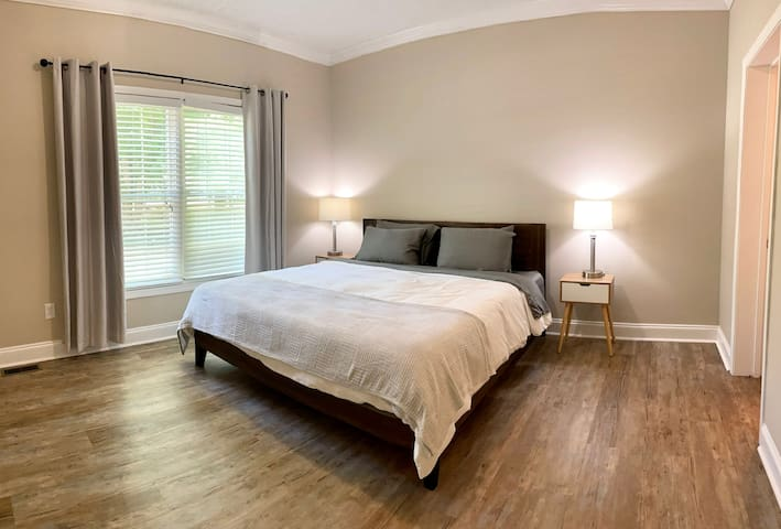 King suite room with a peaceful aesthetic. Very comfortable bed, attached bathroom with a walk-in closet. There will also be a desk and office chair (not pictured).