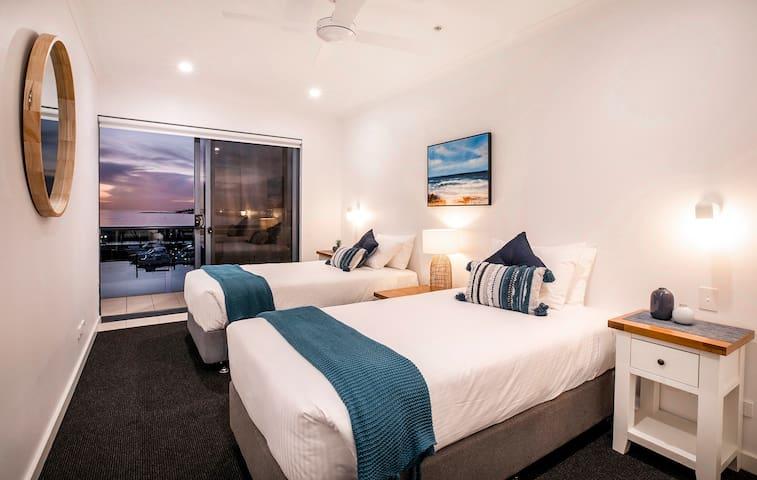 Twin bedroom with balcony and marina views