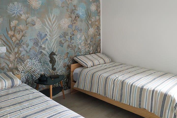 Les 2 chambres sont à l'étage (escalier bois avec rampe d'abordage en cordage). Literies neuves et calme absolu. Lit en 160×200 pour la chambre du Capitaine, deux lits twin en 90×200 pour la chambre des Marins (jumelés sur demande en 180×200)