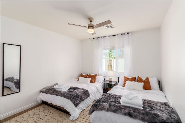 The first of many bedrooms in the house features two full size beds with plush blankets and pillows