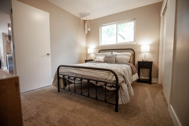 Master bedroom with a queen sized bed and night stands with power to charge electronic devices.