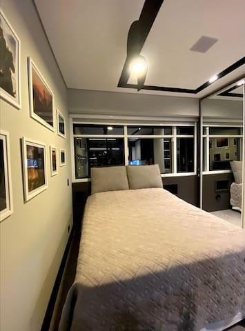 Cama Queen, com duas almofadas grandes e confortáveis para assistir televisão ou leitura, ventilador de teto, espelho grande do chão ao teto.