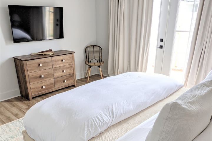 Main floor bedroom furnished with king-size bed and luxurious bedding.   Television is preloaded so guest will have access to Sling, Hulu, Netflix, Disney+, HBO Max, and Amazon Prime Video.