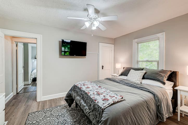 Master bedroom with queen-sized bed and smart tv. Full bathroom accessible through master bedroom