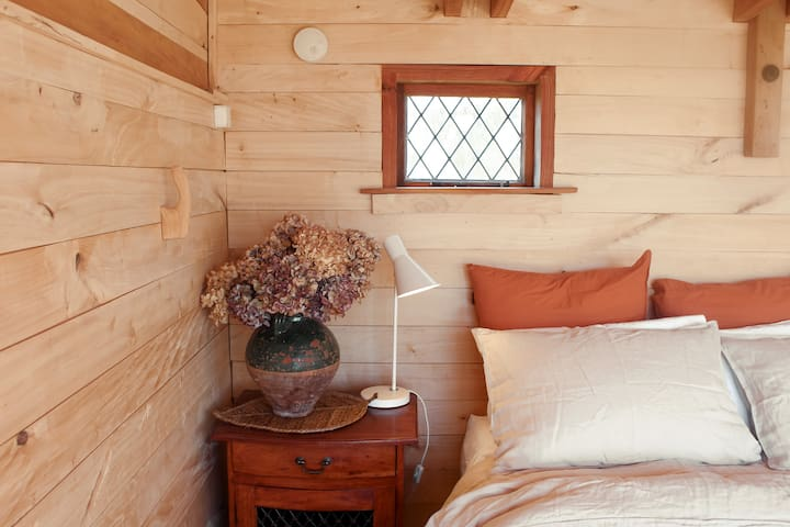 The cabin has a comfortable queen-sized bed. Two bedside cabinets provide storage for your belongings.