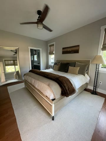 Master bedroom with king bed, walk in closet and rain shower in bathroom