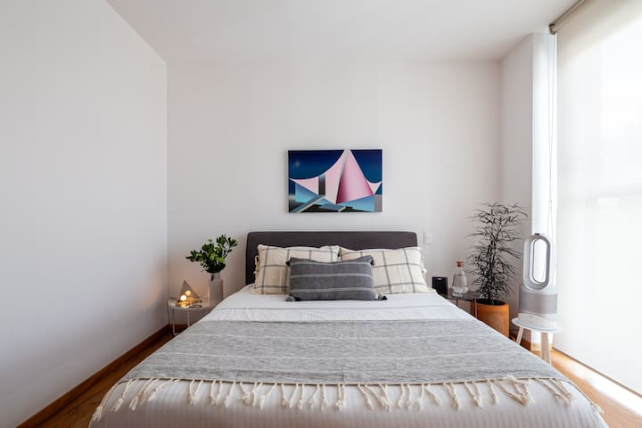 Recámara con cama queen size y purificador de aire.