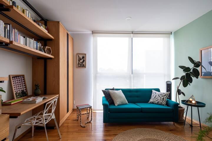 Un tranquilo estudio con sofá cama doble, perfecto para hacer home office.