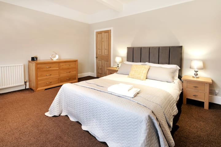 Master bedroom with a comfortable double bed and oak furniture.