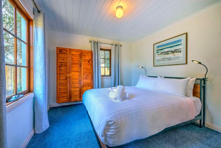 The main bedroom looks out over the water and has a comfortable queen bed, with access to the ensuite bathroom.