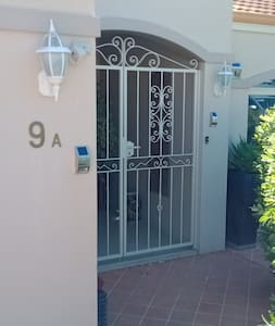 Well lit entrance with double entry gates to wide portico and double front door entry