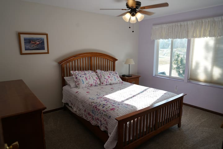 Second bedroom with dresser and queen sized bed.
