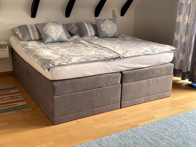 Schlafzimmer 1 mit Boxspringbett und grüßem Einbauschrank, Zugang zur Terrasse