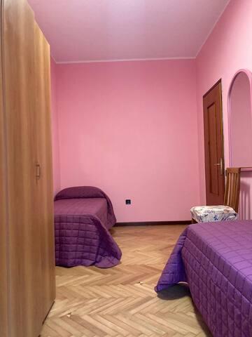 Camera con due letti singoli e un spaziosi armadio. Finestra che si affaccia sul giardino. Pavimento in legno.